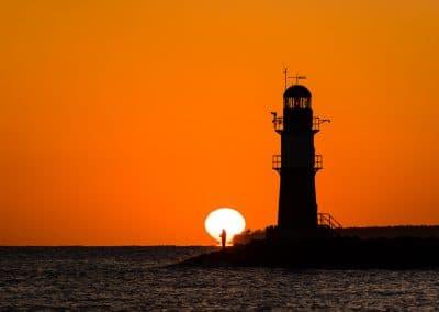 Angler im Sonnenaufgang am Leuchtturm (Ostfeuer) in Warnemünde